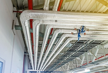 Metal pipes in thermal insulation winding on the ceiling of an industrial enterprise.